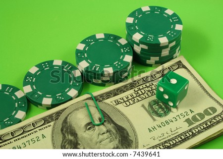 four piles of poker chips and a die over bills of one hundred dollars