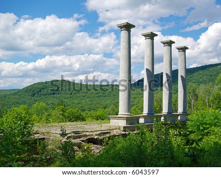 Four pillars stretch toward the sky at the ruins of an old mansion. - stock photo