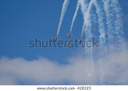four planes fly  in formation with vapor trails against a brilliant blue sky