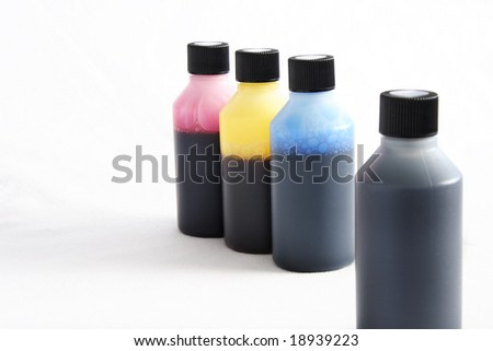 four plastic bottles with different coloured ink in each - stock photo
