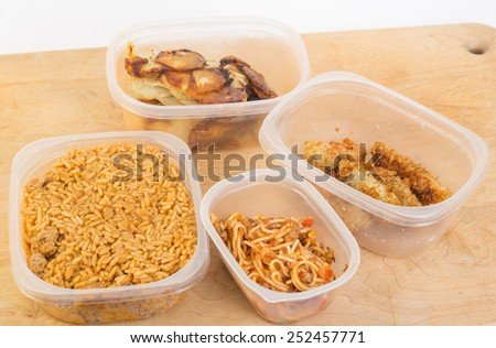 Four plastic containers filled with leftovers - Jambalaya, spaghetti, chicken tenders and onion and potato frittata on wooden cutting board. - stock photo