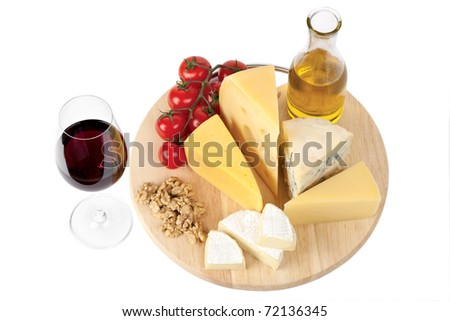 Four popular kinds of cheese, tomatoes and red wine glass on a white background. A shot horizontal, focus in the shot foreground. - stock photo