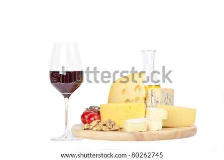 Four popular kinds of cheese, tomatoes and walnuts on a white background. A shot horizontal, focus in the shot foreground. - stock photo