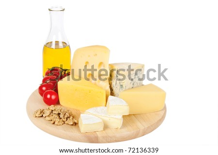 Four popular kinds of cheese, tomatoes, olive oil and walnut on a white background. A shot horizontal, focus in the shot foreground. - stock photo