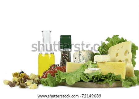 Four popular kinds of cheese, tomatoes, spices, pasta and an olive oil bottle lie on salad sheet on a white background. A shot horizontal, focus in the shot foreground. - stock photo