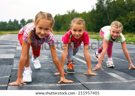 four pre-teen girls starting to run on track - stock photo