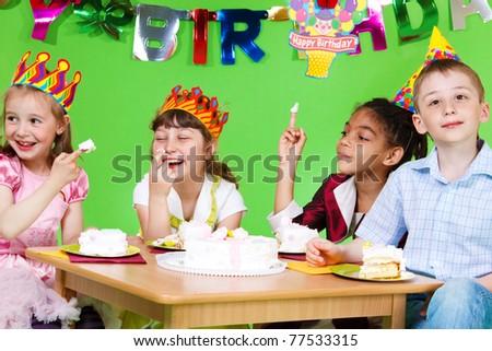 Four preschool kids eating birthday cake - stock photo