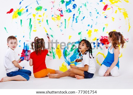 Four preschool kids painting the wall - stock photo