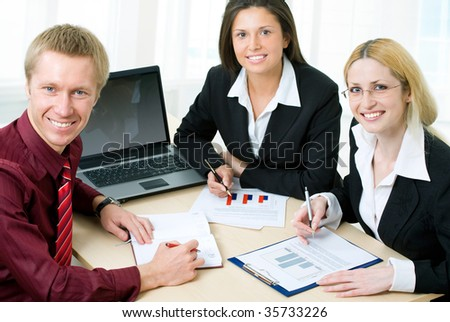 Four professionals looking at camera - stock photo
