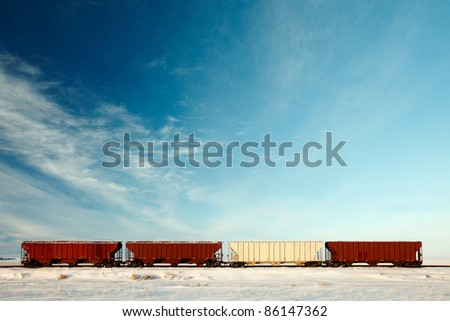 Four railroad hopper cars parked on rural tracks all by themselves on a cold winter day. - stock photo