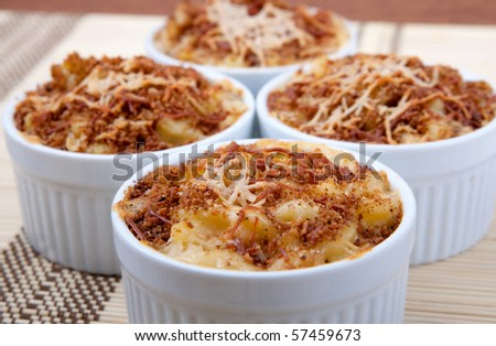 four ramekin bowls of homemade macaroni and cheese dinner topped with brown toasted cheesy crust - stock photo