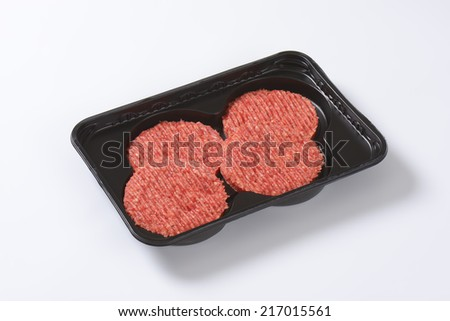 four raw hamburger patties on black plastic tray - stock photo