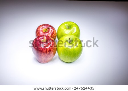 Four red and green apples in square composition painted with light