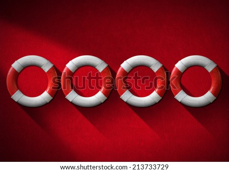 Four red and white lifebuoys hanging to a red velvet wall - Concept of help - stock photo