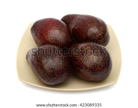 four red avocados on plate isolated on white  - stock photo