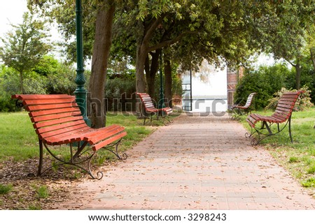 Four red benches in the park - stock photo