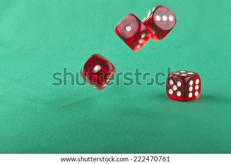 Four red bouncing dice On green background with some shadow - stock photo