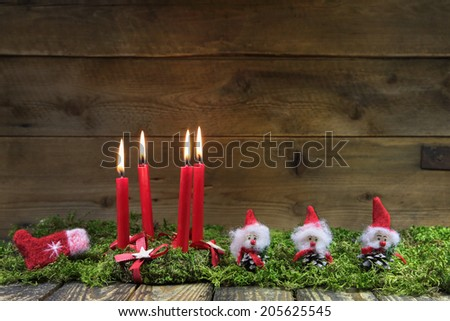 Four red burning christmas candles on wooden background with green moss. - stock photo