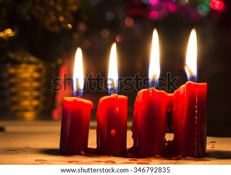 Four red  candles with Christmas decoration light,  bokeh and bur background, night time