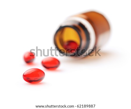Four red capsules spilling out of a pill container. Isolated over white background. - stock photo