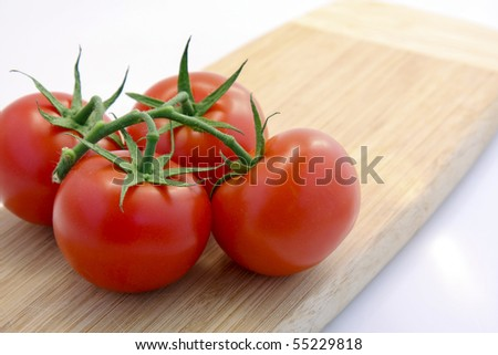 Four Red Tomatoes on a Wooden Cutting Board - stock photo