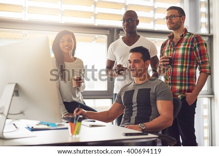 Four relaxed young diverse male and female small business workers with drinks in hand standing around computer in office - stock photo