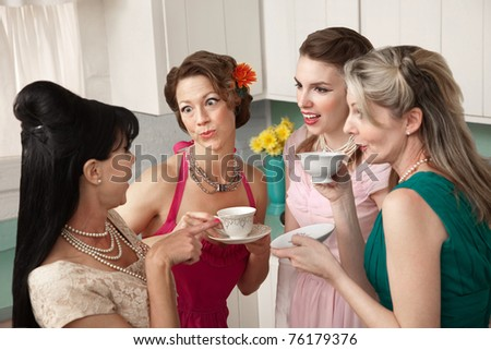 Four retro-styled women chit-chat over coffee in a kitchen - stock photo