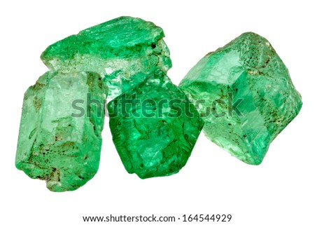 Four rich green emerald crystals on white - stock photo