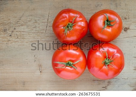 Four ripe tomatoes on wooden board, top view - stock photo