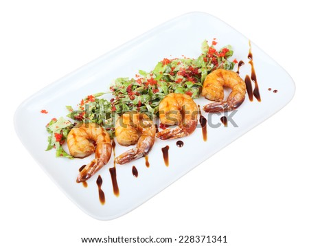 four roasted shrimps with green salad and tobiko on a white rectangular plate isolated on white background.