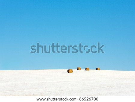 Four round bales of hay in a field in the winter covered with snow. - stock photo
