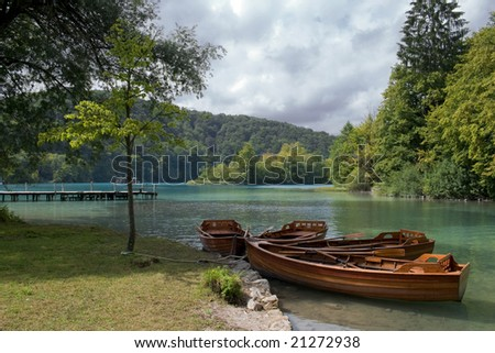 Four row boats tied to a tree on a bank of Plitvice Lakes, Croatia.