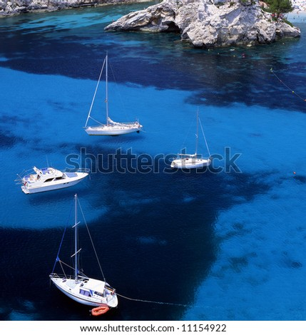 Four sail boats in the waters of Paleokastritsa, Corfu, Greece - stock photo