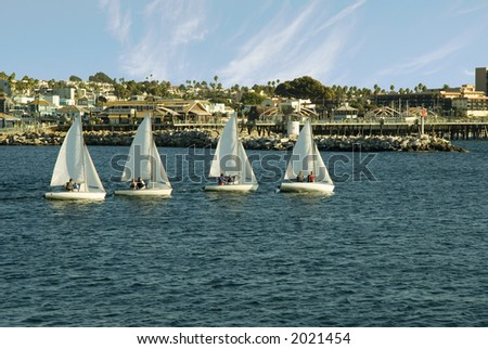 Four sailboats in a harbor sailing in a row during practice - stock photo