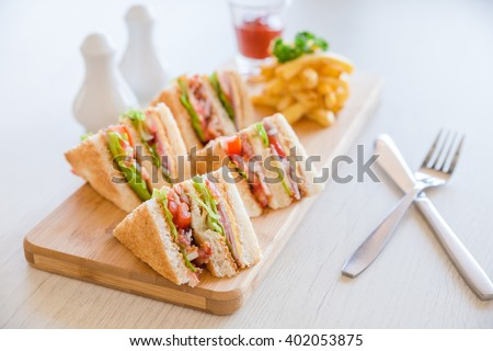 Four sandwiches on the board - stock photo