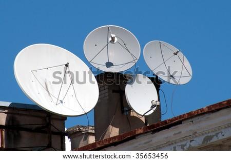 Four satellite dish antennas on the home roof - stock photo