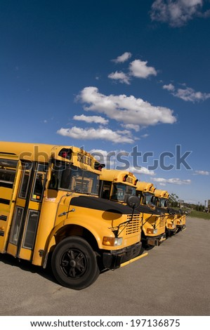 Four school buses lined up in a row.