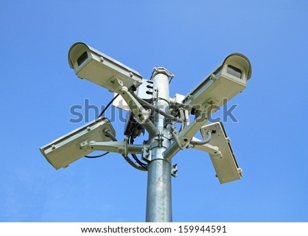Four security cameras against blue sky background  - stock photo