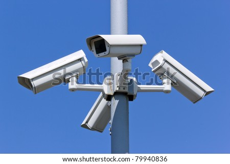 four security cameras on blue sky - stock photo