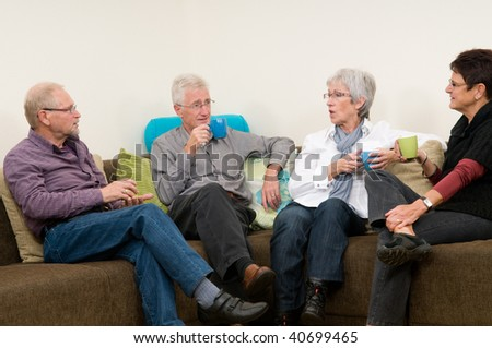 Four seniors discussing some things while drinking coffee - stock photo