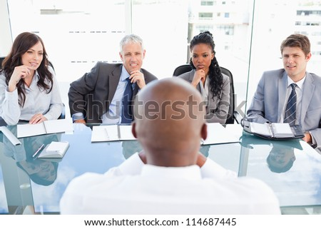 Four serious business people sitting at the desk while listening to explanations