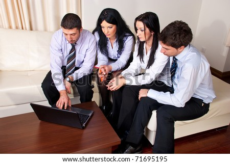 Four serious business people sitting on a couch n a office room and using laptop - stock photo