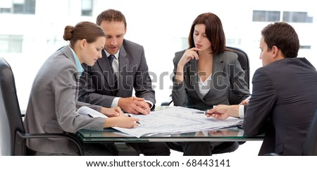 Four serious engineers looking at plans sitting at a table at work - stock photo