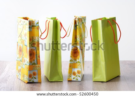 four shopping bags with spring, summer colors and sunflowers