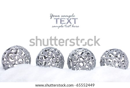 Four silver Christmas ornaments in the snow - stock photo