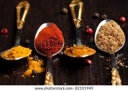 Four silver teaspoons with set of the spices on black table - stock photo