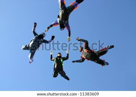 Four skydivers building a star formation - stock photo