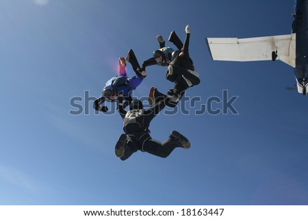 Four skydivers exit a plane as a formation - stock photo