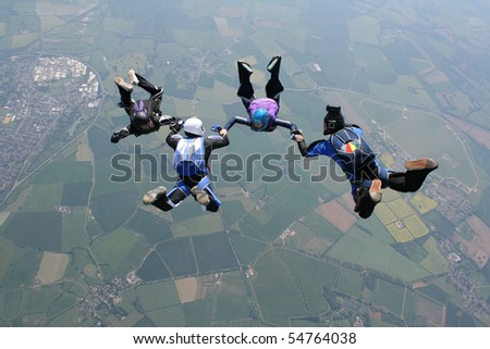 Four skydivers holding hands - stock photo