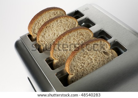 Four slices of brown bread in a stainless steel toaster - stock photo